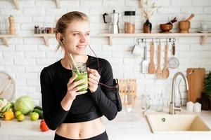 Woman drinking green smoothie from mason jar at home kitchen photo