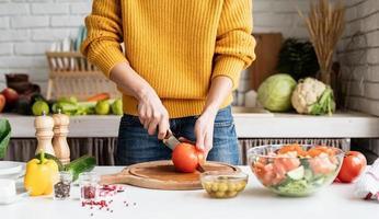 Manos femeninas haciendo ensalada cortando tomates en la cocina foto