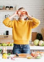 Mujer divertida jugando con tomates, haciendo ensalada en la cocina foto