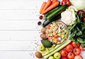 Ensaladera, frutas y verduras sobre fondo blanco de madera foto
