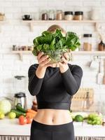 Smiling woman holding a bowl of fresh spinach in the kitchen photo