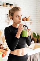 Mujer bebiendo batido verde de mason jar en la cocina de casa foto