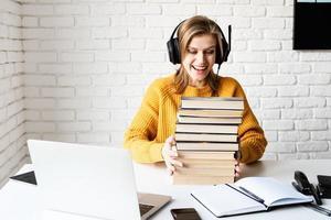 mujer en auriculares negros estudiando en línea y sosteniendo una pila de libros foto