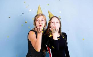 Las mujeres jóvenes sosteniendo globos celebrando un cumpleaños sobre fondo azul. foto