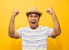 Feliz joven asiático celebra con dos manos en el aire foto