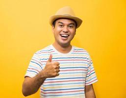 Joven asiático con sombrero se siente feliz y sorpresa mostrando el pulgar hacia arriba foto