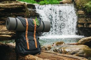 Hipster hiker tourist backpack on background of river and waterfall photo