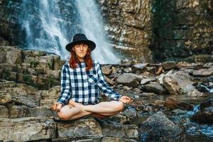 Mujer con sombrero y camisa meditando sobre rocas en posición de loto foto