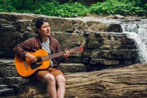 hombre tocando la guitarra sentado junto a una cascada foto