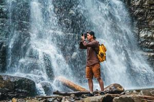 Man taking a photo of a waterfall