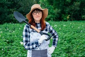 Woman posing with a shovel photo