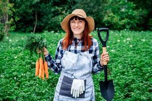 Woman holding carrots and shovel photo