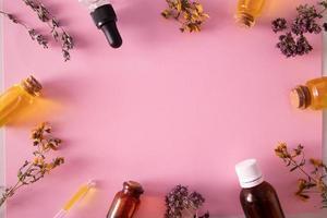 Hierbas secas y botellas de aceite o tintura vista superior foto