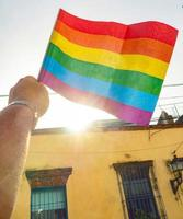 A hand holds a rainbow flag of the LGBTQ movement, house in background photo