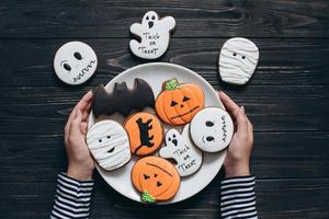 A girl preparing for Halloween and holding plate with gingerbreads. photo