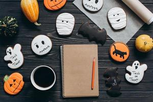 Cup of coffee, gingerbread for Halloween, notebook and pumpkins. photo
