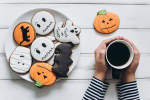 Female preparing for Halloween, drinking coffee with gingerbread photo