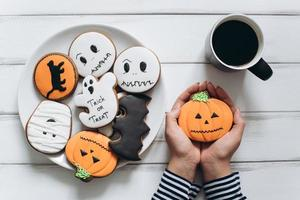 Female preparing for Halloween and eating scary gingerbread cookies. photo
