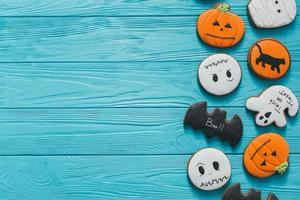 Fresh halloween gingerbread cookies on blue wooden table. photo