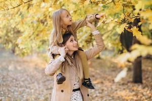 Mother and her daughter have fun and walk in the autumn park. photo