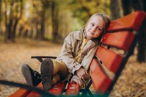 una niña con un vestido amarillo y un abrigo beige camina en el parque de otoño foto