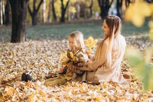 Mother and her daughter sitting and having fun in the autumn park. photo