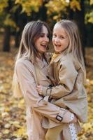 madre y su hija se divierten y caminan en el parque de otoño. foto
