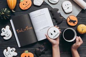 Girl holding cup of coffee, gingerbread for Halloween photo