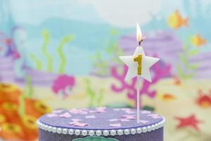 Lighted birthday candle in star shape with blurred background photo