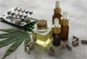 pastillas de cbd. grupo de cápsulas claras de cbd cannabidiol, aceite y hojas de cáñamo foto