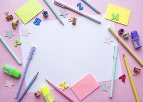 Marco de diferentes artículos de papelería sobre fondo rosa. foto