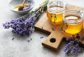 Jars with honey and fresh lavender flowers photo