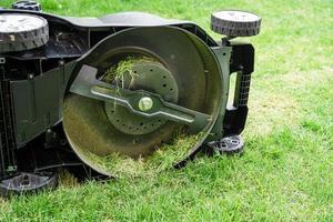 Cuchilla en la máquina cortadora de césped cortada hierba verde foto