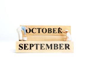 Gente en miniatura, trabajador pintando octubre en bloque de madera sobre fondo blanco. foto