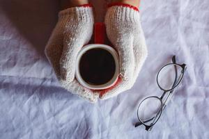 Red coffee cup in hand wearing gloves in winter photo