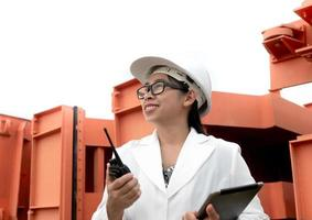 Female engineer in a white helmet talking radio. photo