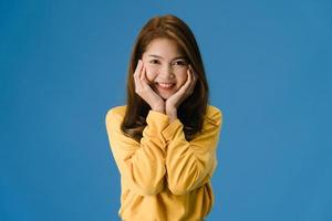 Young Asian lady with positive expression on blue background. photo