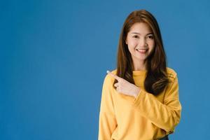 joven asiática sonriendo con expresión alegre fondo azul. foto