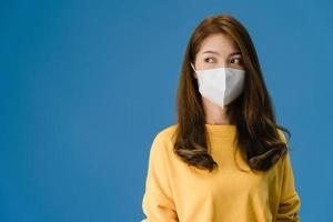 Young Asian girl wearing medical face mask on blue background. photo