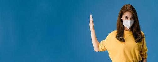 Joven asiática usa mascarilla haciendo señal de stop sobre fondo azul. foto