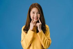 Señora joven de Asia que muestra una sonrisa, expresión positiva sobre fondo azul. foto