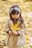 Little girl offended holding a yellow maple leaf in autumn park photo