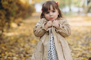 Little girl in a beige coat shows emotions in the autumn park photo