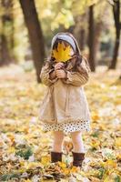 Happy little girl holding a yellow maple leaf in the autumn park photo