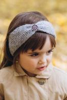 Happy little girl in a beige coat walks in the autumn park photo