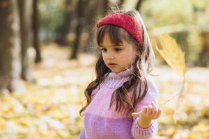Portrait of a happy little girl holding a leaf in the autumn park photo