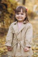 Hermosa niña con un abrigo beige camina en el parque de otoño foto