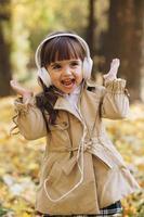 Happy little girl listening to music on headphones in the autumn park. photo