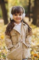 Happy little girl listening to music on headphones in the autumn park photo