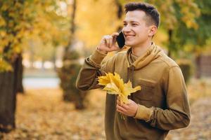 chico feliz sonriendo y hablando por teléfono en el parque de otoño foto